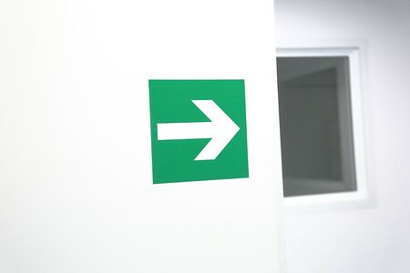 Green pointer to turn right on a white wall 写真素材