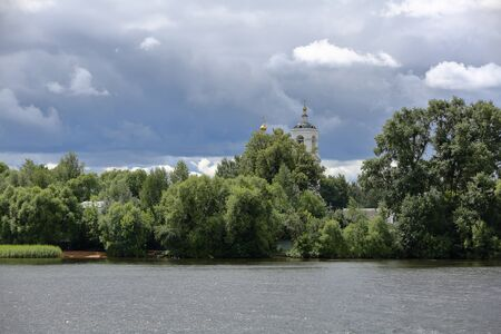 The golden dome of the white stone Orthodox church on the bank of the river