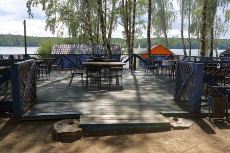 Part of a cozy beach cafe without visitors on the banks of the summer river 写真素材