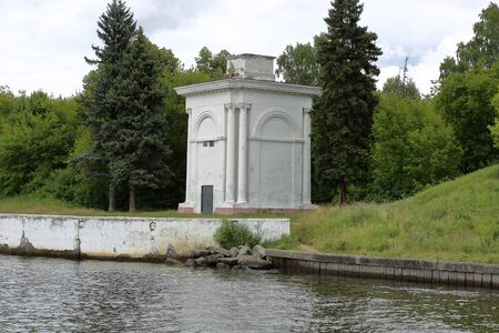 White stone building of the old river pier on the shore against the background of green forest