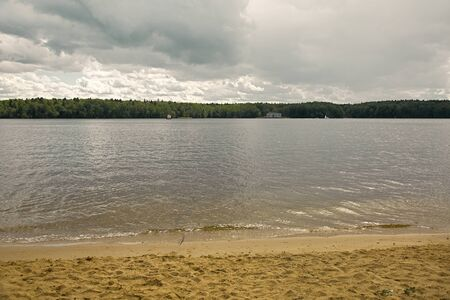Sandy shore, calm river with sailboats and a summer forest against a cloudy sky