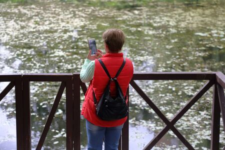 Mature woman with short hair in a red vest photographs a pond with duckweed using a smartphone Фото со стока