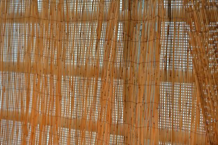 Craft blinds made of thin brown bamboo in the doorway Imagens