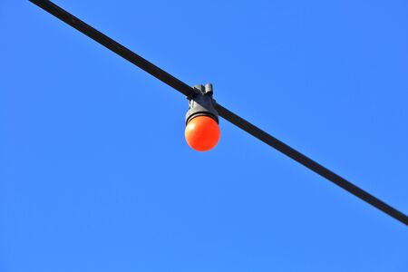 Bright light bulb on a black street wire against a blue cloudless sky in the daytime