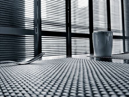 Empty table with a fork and a cup on the background of closed shutters