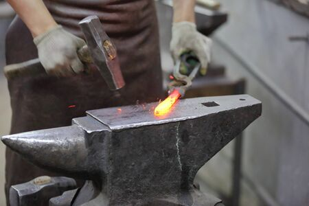 Forging an iron handmade product in a craft forge workshop