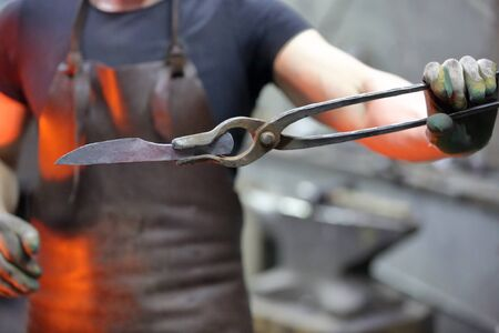 Worker in the blacksmith shop shows tongs with forged preheated workpiece 免版税图像