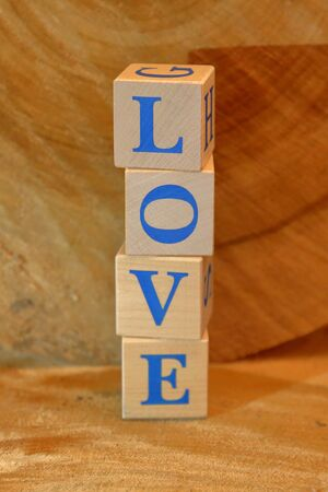Wooden cubes with word LOVE on a natural wood background Standard-Bild
