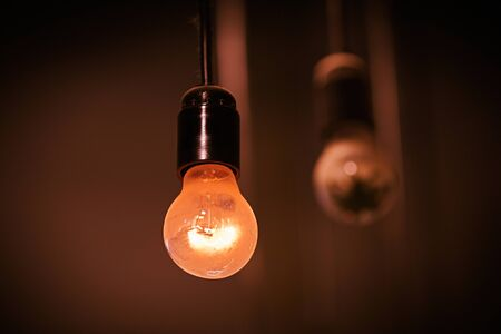 A simple light bulb lit on a black wire