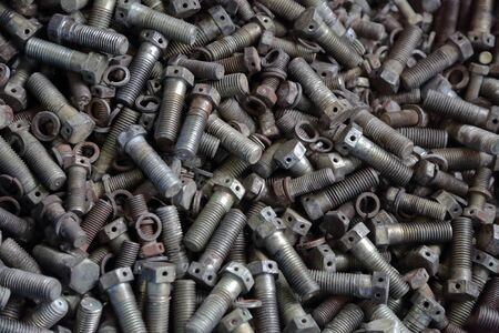 Different steel bolts piled in a heap in an industrial workshop