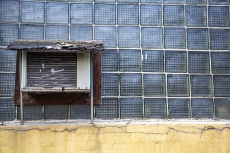 Broken retro air conditioning on a wall of glass blocks Stock Photo