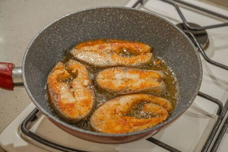 A steak of delicious fish varieties is fried in a frying pan on a kitchen gas stove