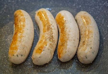 Appetizing ruddy juicy Munich sausages fried in a pan. Bavarian food style Stock Photo