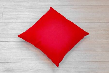 Square red pillow on natural wood floor
