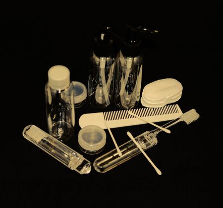 Cosmetic plastic travel set allowed for air transportation on a dark background