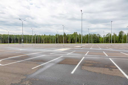 Empty free outdoor parking near the shopping mall on a cloudy summer day