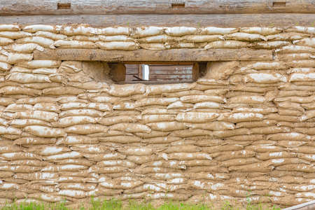 Wooden house with a wall of sandbags. Military fortification and a place for targeted shooting