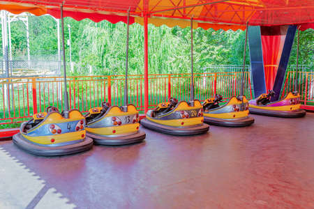 Attraction in the city summer park. Vacant electric colorful cars for kids