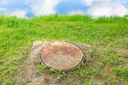 Old round manhole among lush green grass Archivio Fotografico