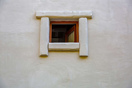 Part of the surface of the outer wall of a building with an old wooden window
