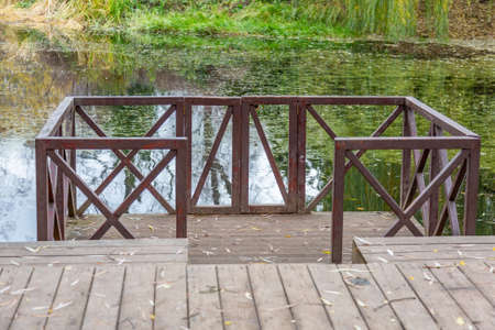 A small wooden pier for boats at the abandoned city pond with duckweed Stock fotó