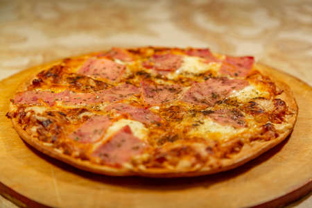 Textured surface of cheese pizza with spices. Homemade fresh baking recipe
