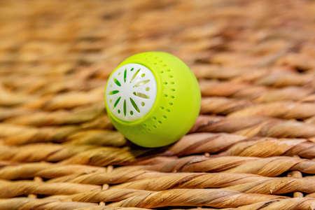 Bright green ball-shaped odor absorber. Home refrigerator gadget