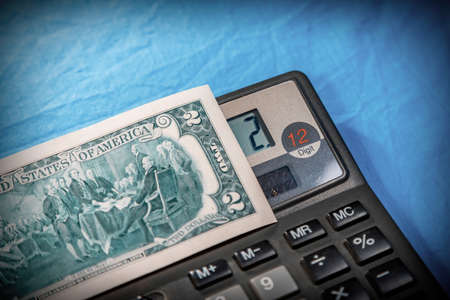 Part of a two dollar American bill and a compact digital calculator on a fabric blue background Stock fotó