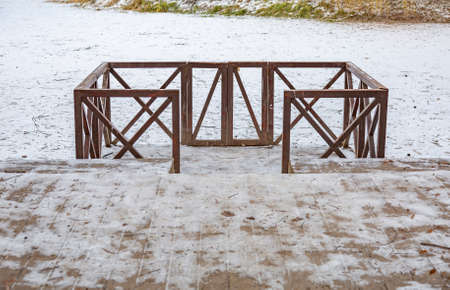 A small wooden pier for boats by a frozen pond with snow