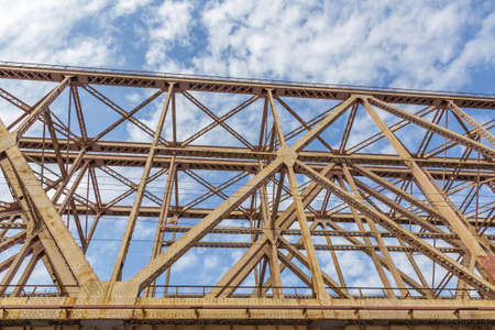 Railway transport bridge made of steel piles and beams against blue sky