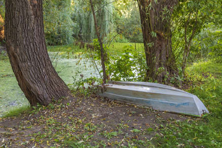 Old abandoned iron boat near a duckweed pond in the daytime