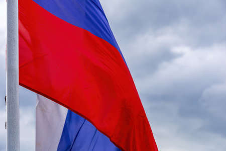 The tricolor state flag of Russia on a cloudy sky background Standard-Bild