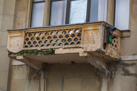 Old stone balcony with traffic lights. Part of an old industrial building