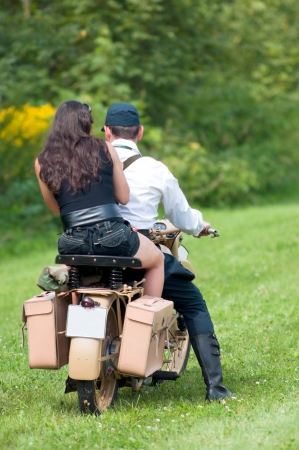 Young couple riding old motorcycle on the grass photo