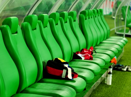 green soccer bench with backpack and sport shoes photo