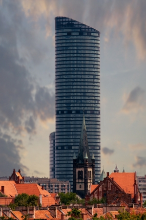 the highest building in wroclaw in combination with the old church Stock Photo