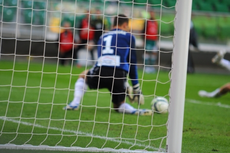 Soccer game seen through net, low angle view