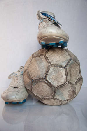 damaged soccer ball with two old  shoes Stock Photo