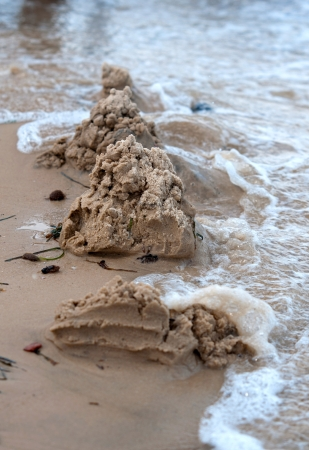 Sand castle destroyed by water wave Stock Photo