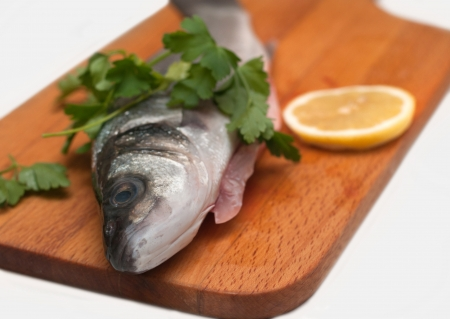 Pike perch on a wooden kitchen board isoleted on white photo