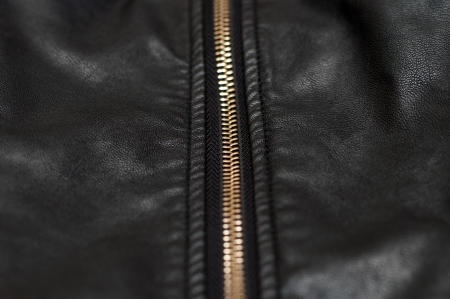 undressing: Close up of zip on black leather material