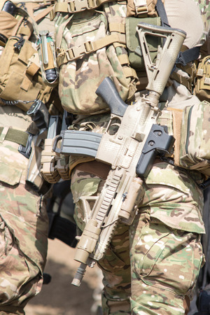 Soldiers in US Army Special Forces uniform, close up on rifle photo
