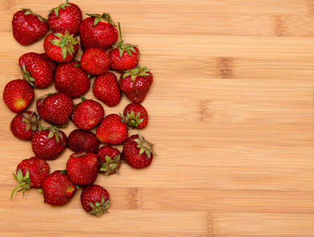red strawberries on wooden table photo