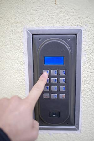 intercom: Human finger pushing button of house intercom