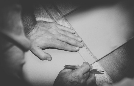 vintage photo of worker using ruler to draw a line marking on a wood board