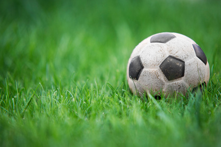 Old and classic Soccer ball or football ball on green field Stock Photo