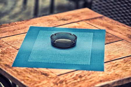 ashtray: Empty glass ashtray on a wooden table. Stock Photo