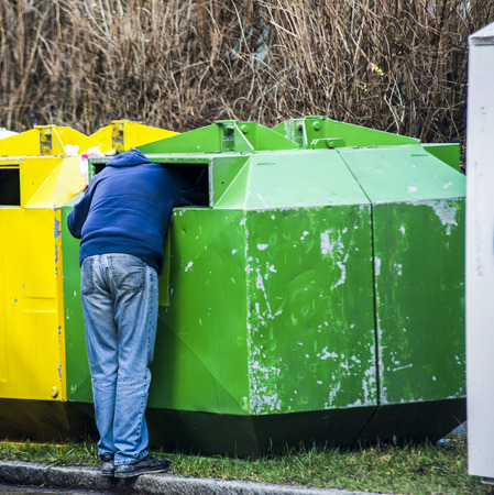 pauperism: Homeless man is searching for food in garbage