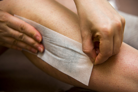 waxed legs: Amateur woman getting legs waxed for hair removal in home Stock Photo