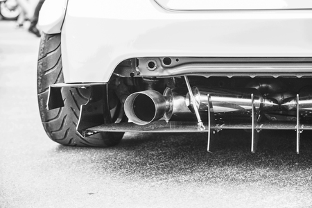 Double exhaust pipes of a modern sports car, black and white Фото со стока